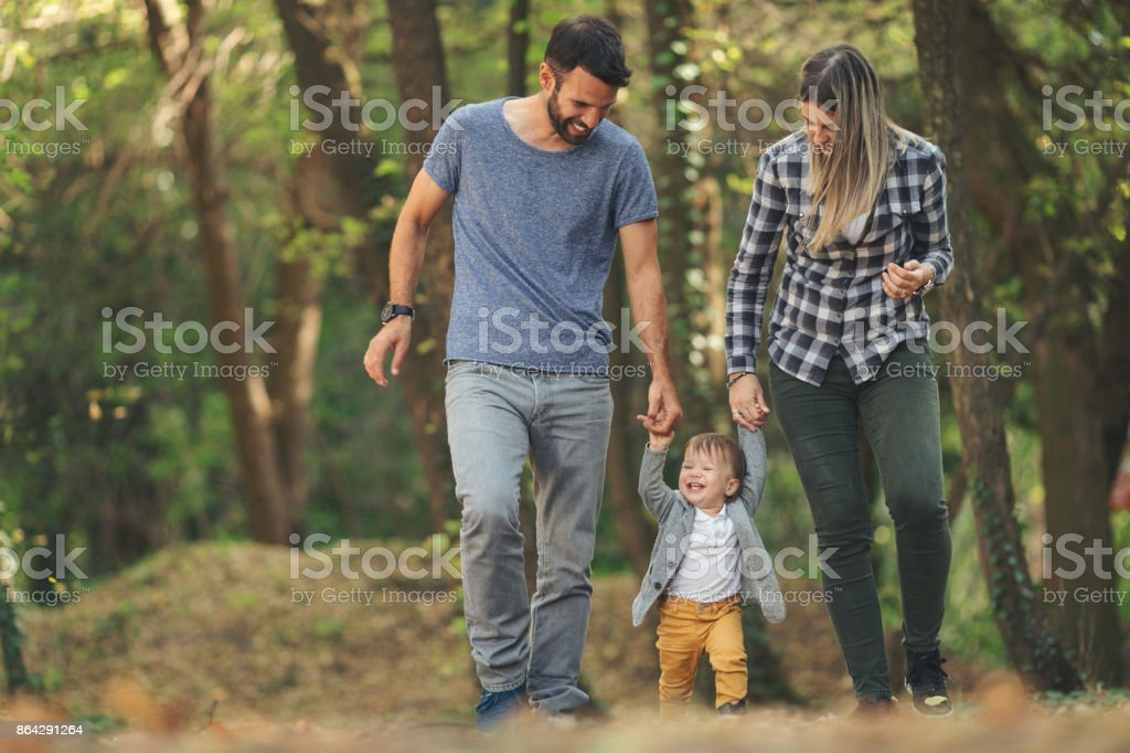Mother and father outdoors teaching baby boy to walk stock photo