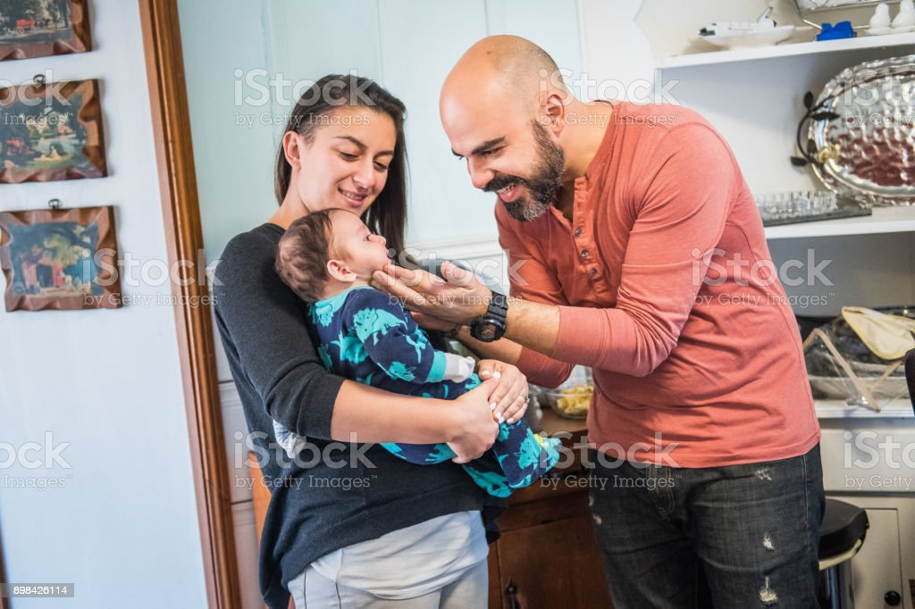 Mother and Father play affectionately with toddler stock photo