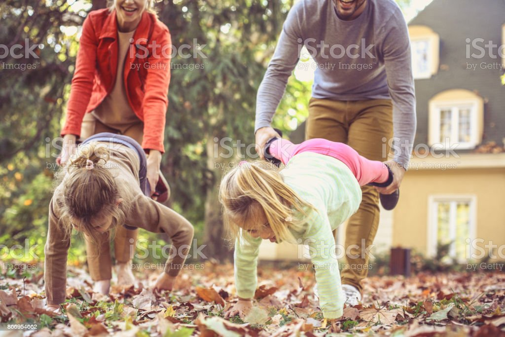 Mother and father playing with daughters at house backyard. stock photo