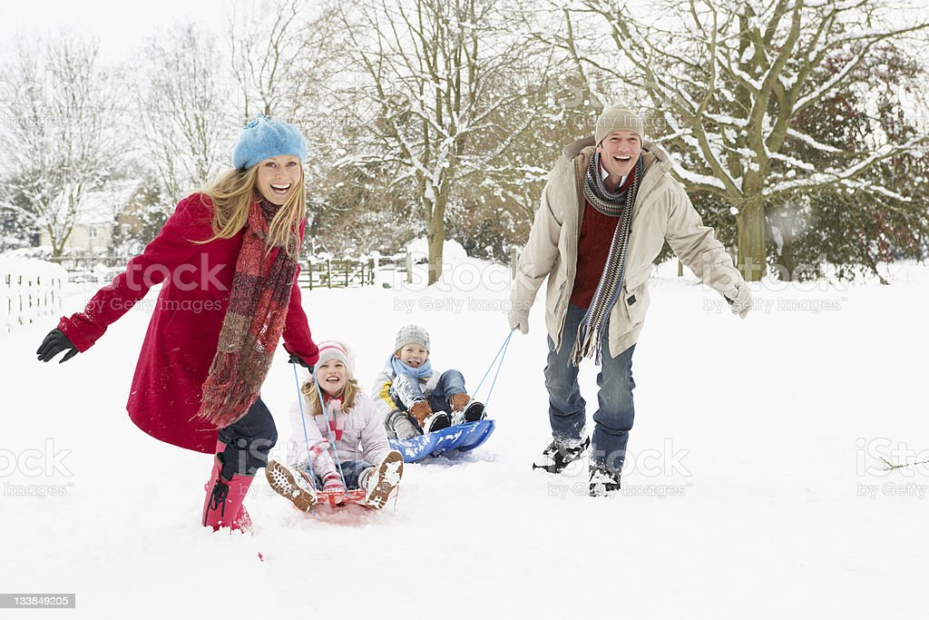 Mother And Father Pulling Children On Sledge stock photo