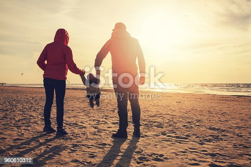 mother and father swinging child by the arms on the beach at sunset