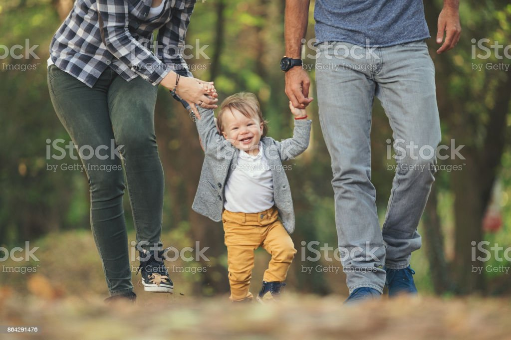 Mother and father teaching baby boy to walk closeup shot royalty-free stock photo
