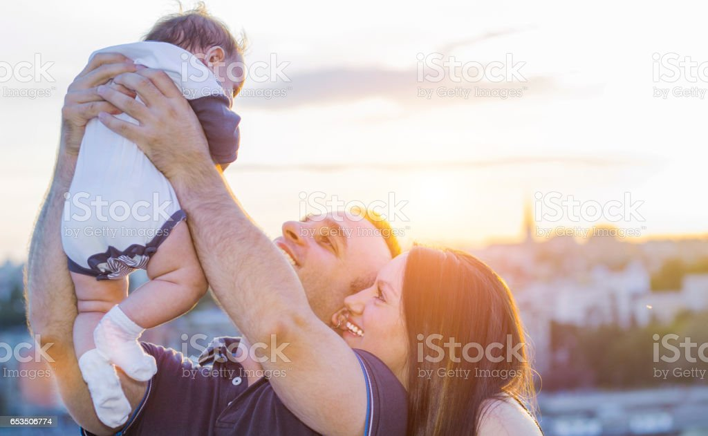 Mother and father with baby in the city stock photo