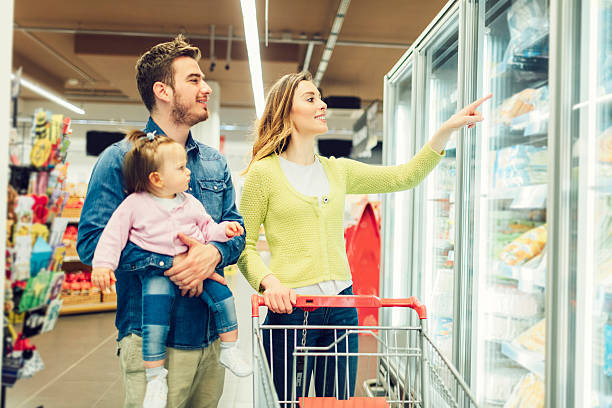 mother and father with their baby daughter grocery shopping - happy person buy appliances stock photos and pictures