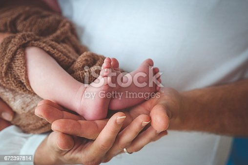 Mother and Father´s Hand Holding Baby´s Legs