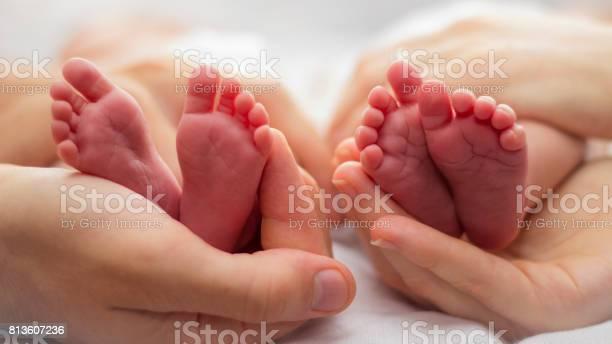 Mutter Und Des Vaters Hände Wiegt Zwei Babys Füße Auf Einem Blassen Hintergrund Stockfoto und mehr Bilder von Zwilling