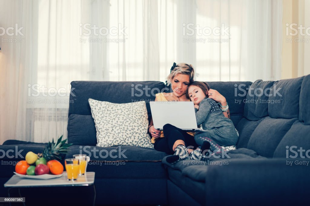 Mother and five year old daughter in bed with laptop stock photo