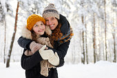 Waist up portrait of loving mother embracing cute little girl in winter forest and smiling at camera, copy space