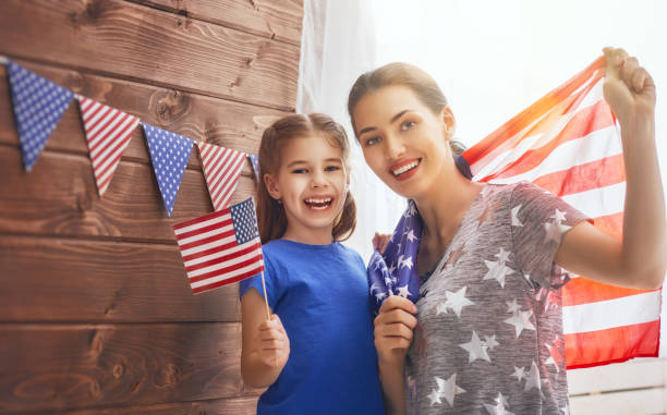 mother and girl with American flag stock photo
