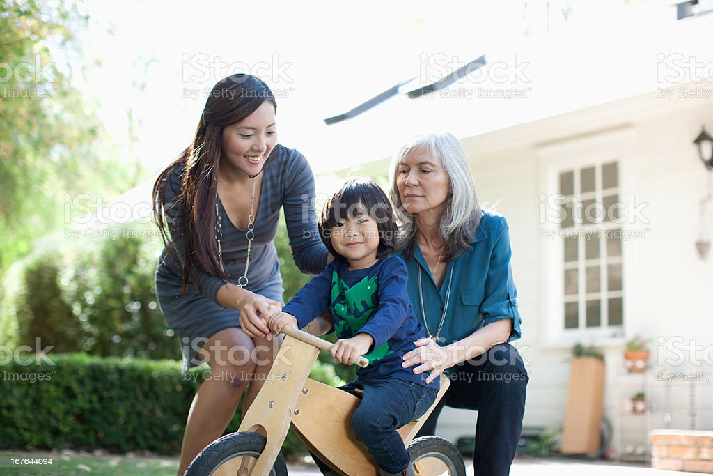Mother and grandmother pushing boy on tricycle stock photo