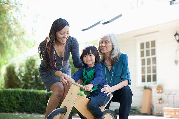 Mother and grandmother pushing boy on tricycle  old mother son asian stock pictures, royalty-free photos & images