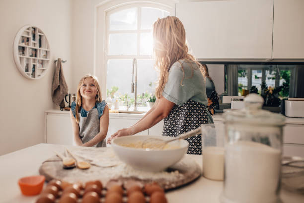 Mother and happy daughter in kitchen stock photo