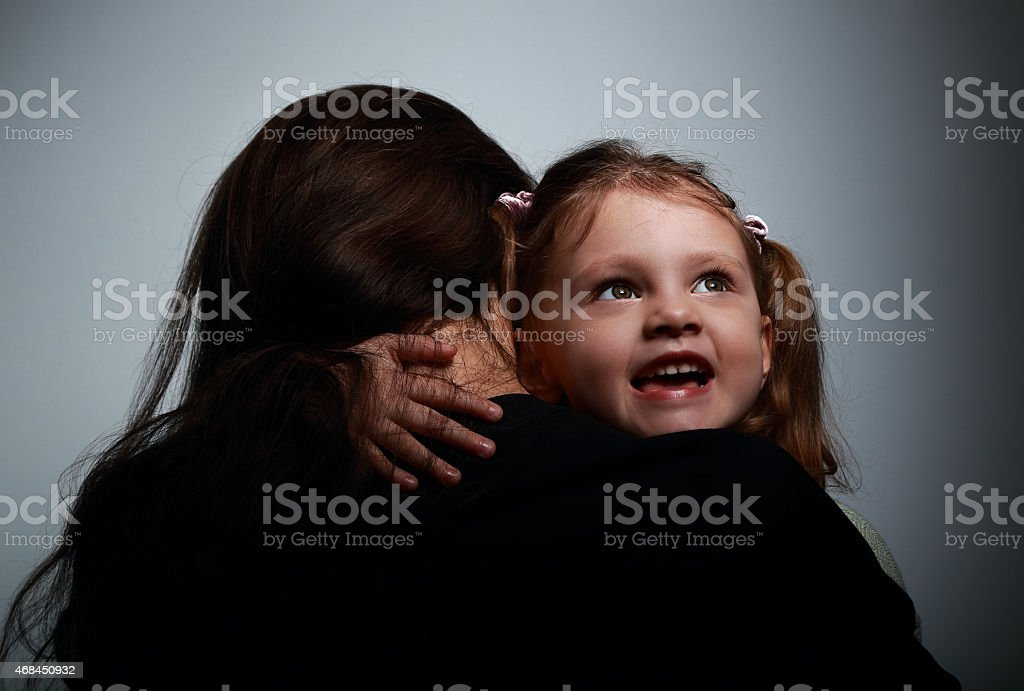 Mother and happy smiling daughter hugging on dark stock photo