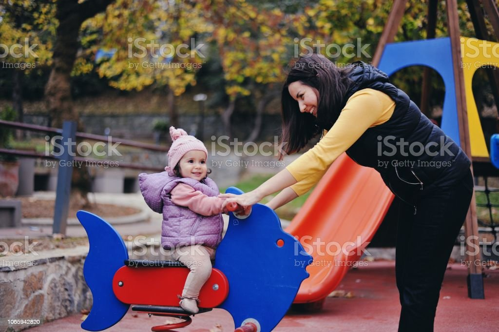 Mother and her 11 months old girl baby playing at a park in autumn stock photo