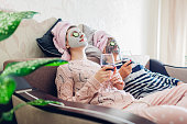 istock Mother and her adult daughter applied facial masks and cucumbers on eyes. Women chilling while having wine 1060199832