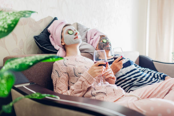 Mother and her adult daughter applied facial masks and cucumbers on eyes. Women chilling while having wine Mother and her adult daughter applied facial masks and cucumbers on eyes. Women chilling while having wine sitting on couch at home sunday stock pictures, royalty-free photos & images