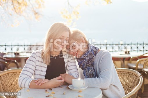 Mother and her adult daughter are hugging. Beautiful women in autumn street cafe outside. Happy senior woman and girl are smiling. Concept of kindness, care, family love, relationships.