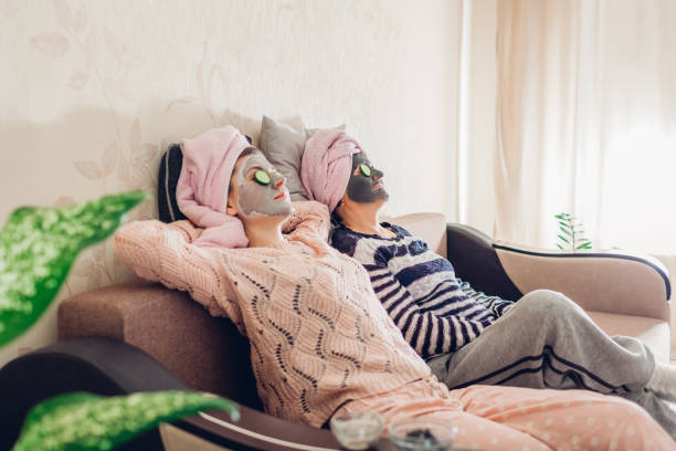 Mother and her adult daughter relaxing with facial masks and cucumbers applied. Women chilling and having fun at home stock photo