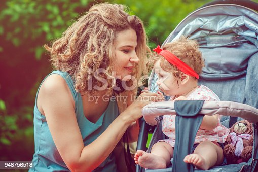 Mother and her baby daughter enjoying summer in park