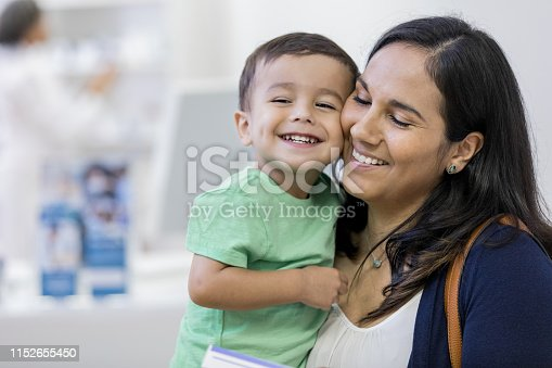 A toddler smiles as he presses cheeks with his mother at the store. His mother smiles and closes her eyes contentedly.
