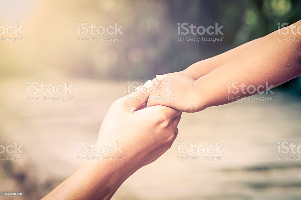 Mother and her child holding hand together with love stock photo