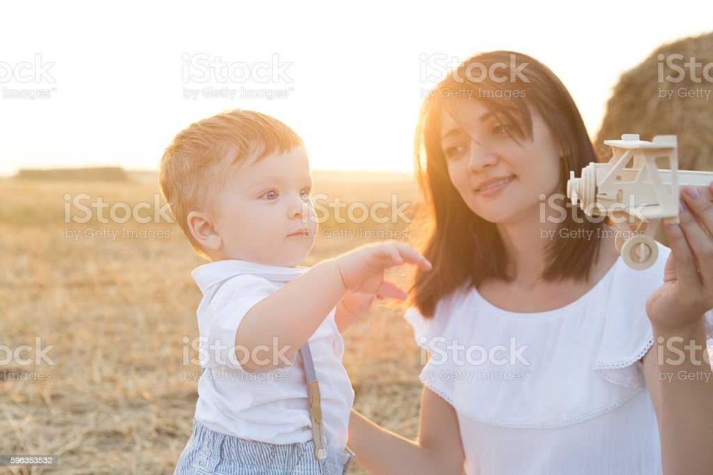 Mother and her child playing in field with toy airplane. royalty-free stock photo