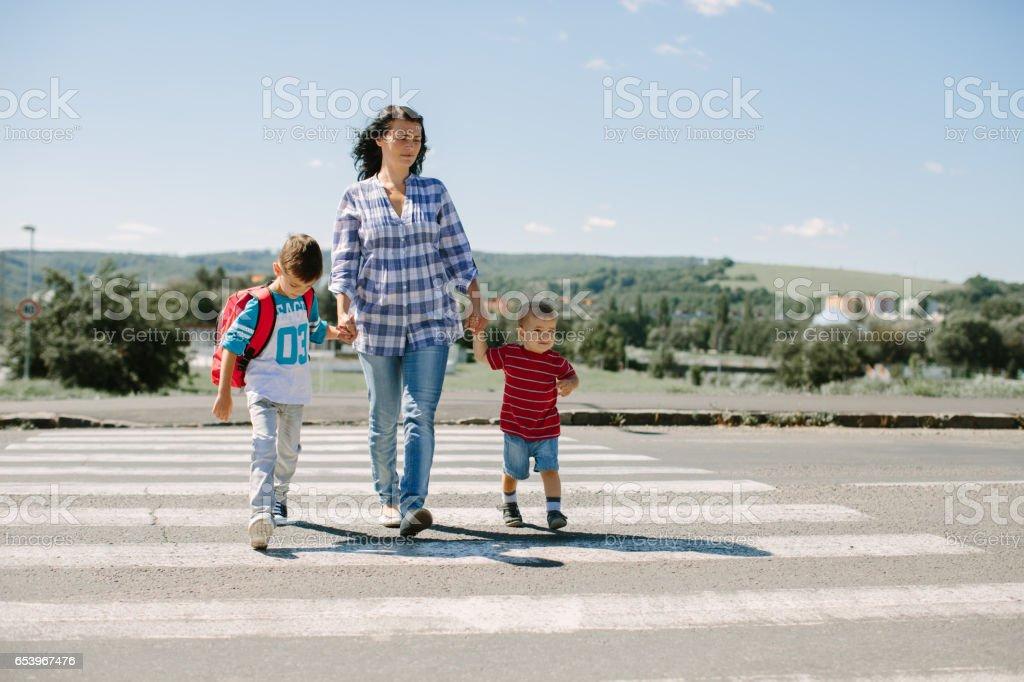 Madre y sus hijos cruzando un camino en el camino a la escuela en la mañana - Foto de stock de Acera libre de derechos