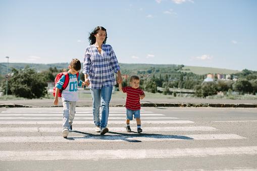 Madre Y Sus Hijos Cruzando Un Camino En El Camino A La Escuela En La Mañana Foto de stock y más banco de imágenes de Acera