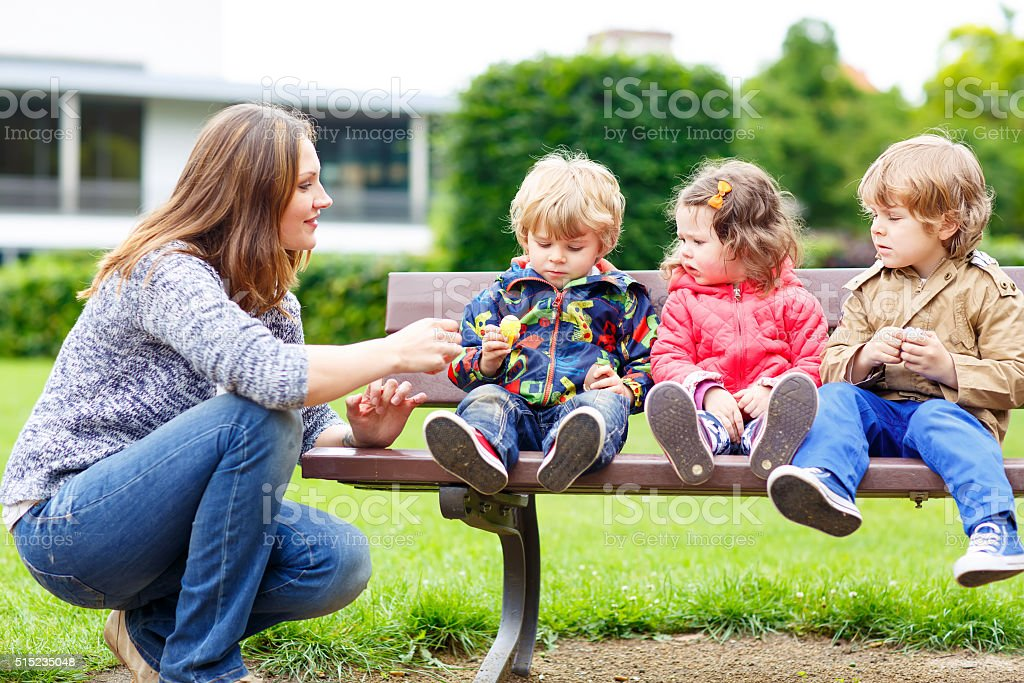 Mother and her children in summer park stock photo