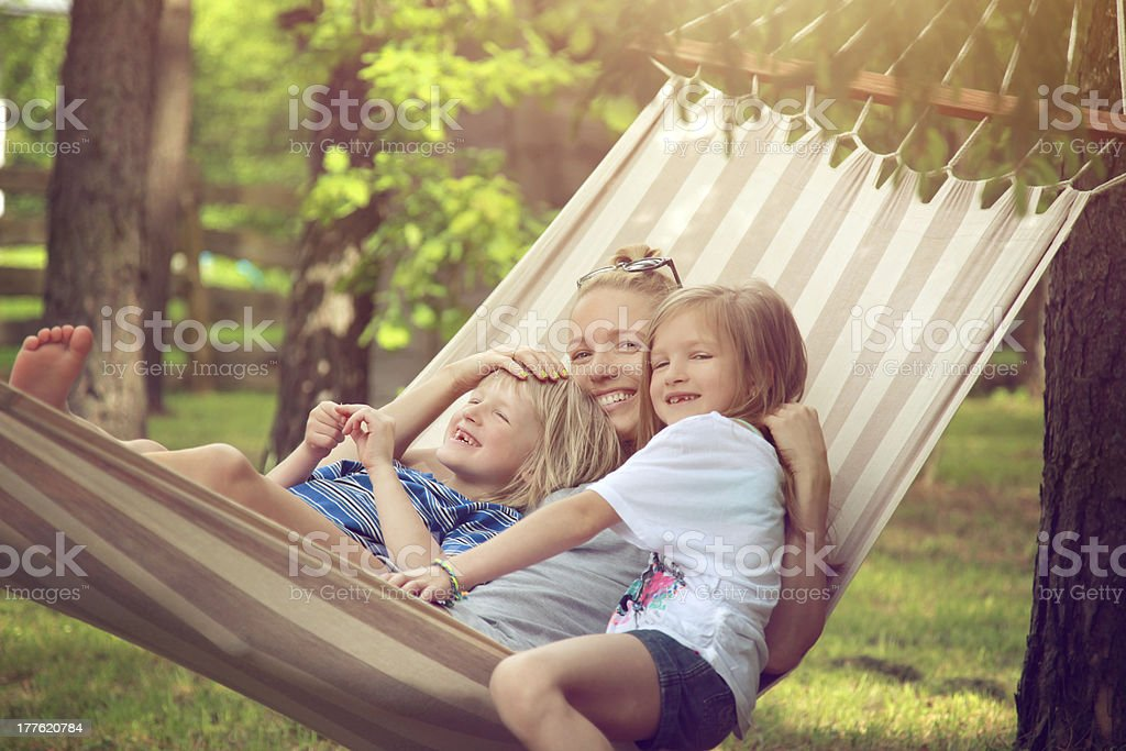 A mother and her children relaxing in a hammock royalty-free stock photo