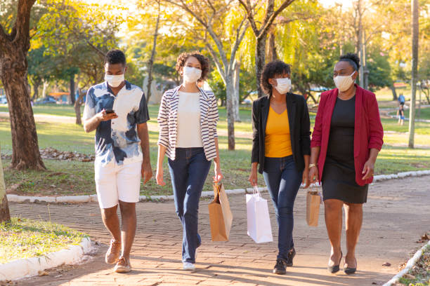 mother and her children shopping using protective masks - afro latino mask imagens e fotografias de stock