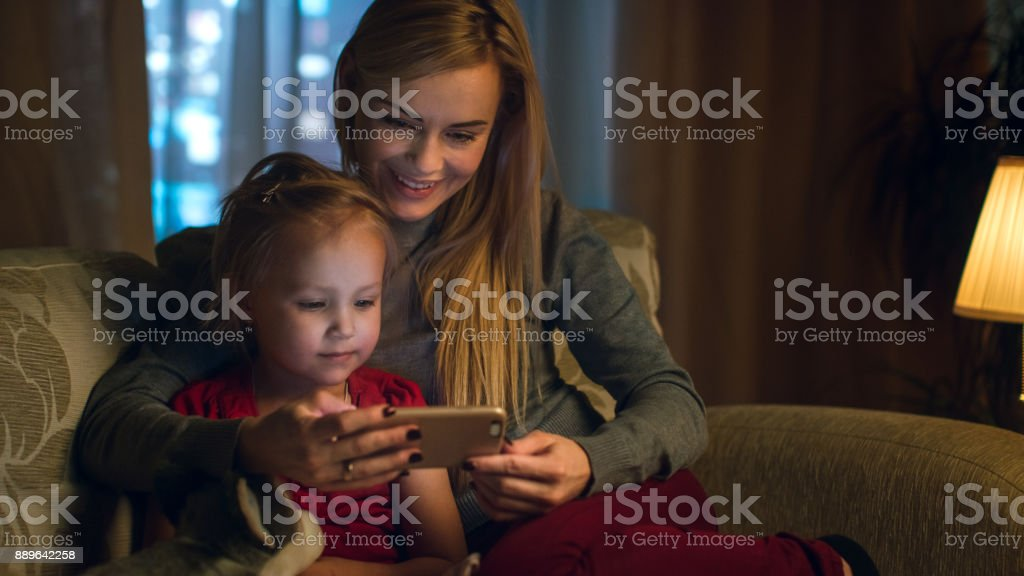Mother and Her Cute Daughter are Sitting On a Couch in the Living Room. They're Using Smartphone and Smiling. It's Evening. stock photo