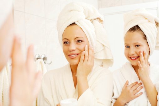 Beautiful mother and her daughter with their hair wrapped in a towel are putting on face cream in the bathroom.