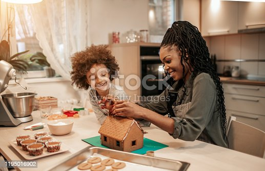Cute 5 years old girl and her mom assemble gingerbread house for Christmas.