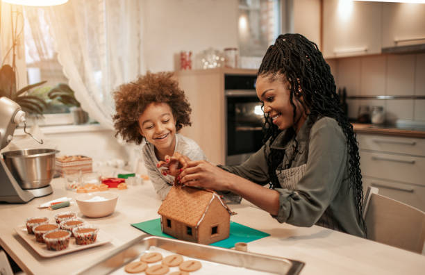 Mother And Her Daughter Assemble Gingerbread House