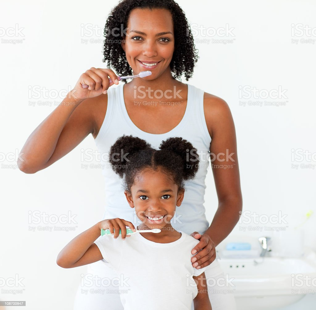 Mother and her daughter brushing their teeth royalty-free stock photo
