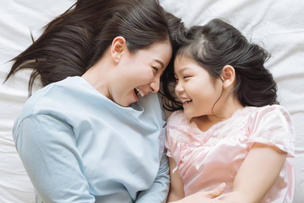 母と彼女の娘の子供の女の子が寝室で遊んでいます。幸せなアジアの家族 - 母娘 笑顔 日本人 ストックフォトと画像