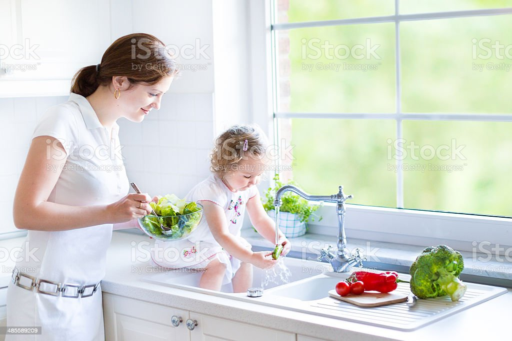 Mother and her daughter cooking salad in kitchen with window stock photo