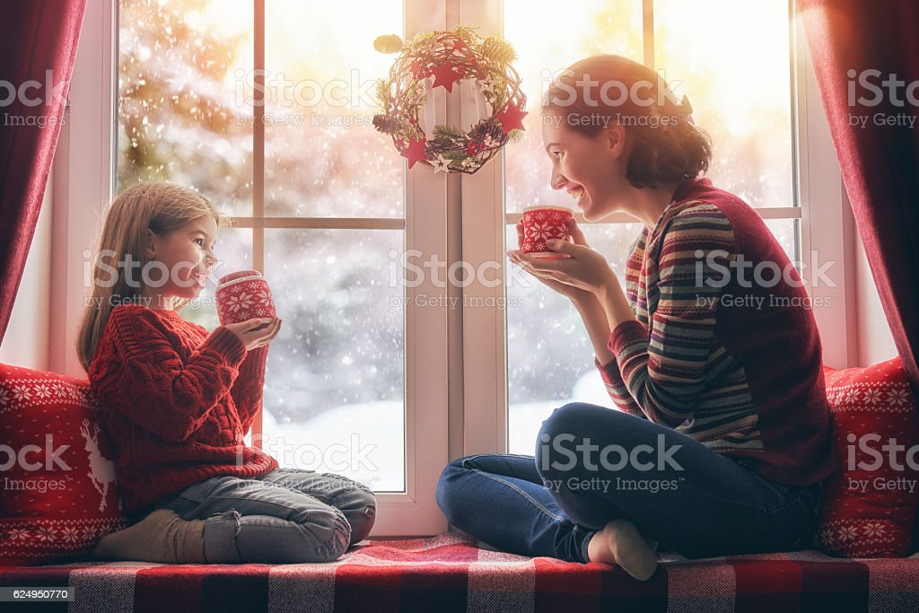 mother and her daughter enjoying hot tea stock photo