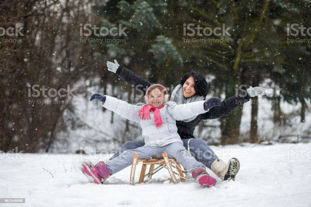 Mother and her daughter enjoying in snow stock photo