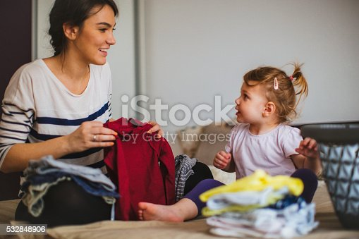 Mother and her daughter folding laundry together