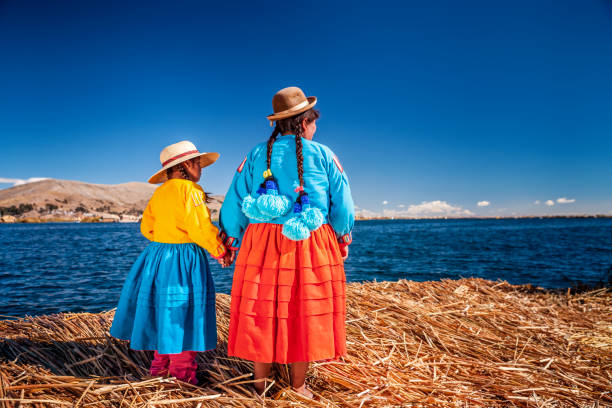 Mother and her daughter looking at view on Uros floating island, Lake Tititcaca, Peru stock photo