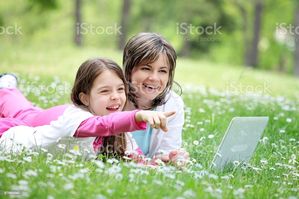 Mother and her daughter lying down with laptop outside. royalty-free stock photo