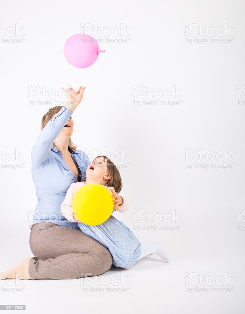 Mother and her daughter playing with a balloon stock photo