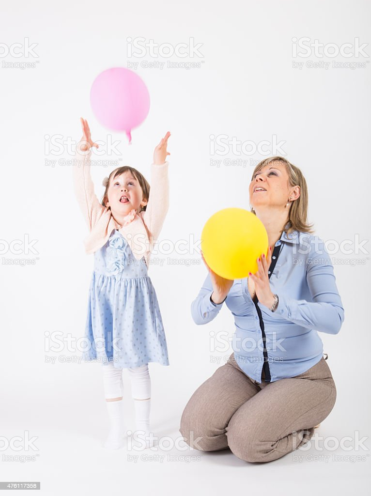 Mother and her daughter playing with two balloons stock photo