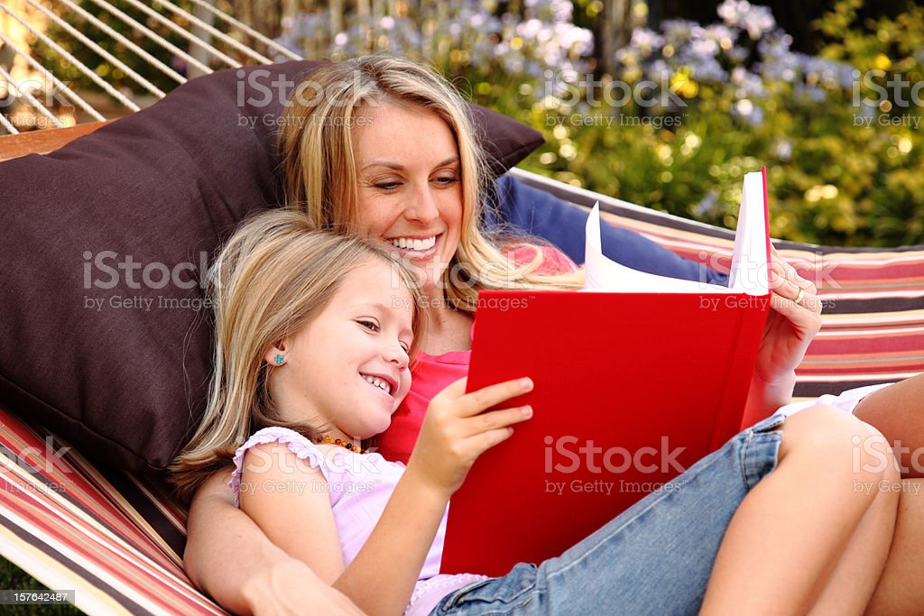 A mother and her daughter reading a big book in a hammock stock photo