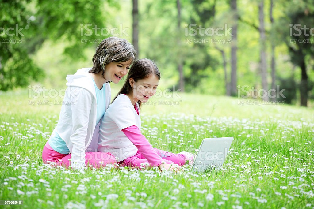 Mother and her daughter sitting with laptop outside. royalty-free stock photo