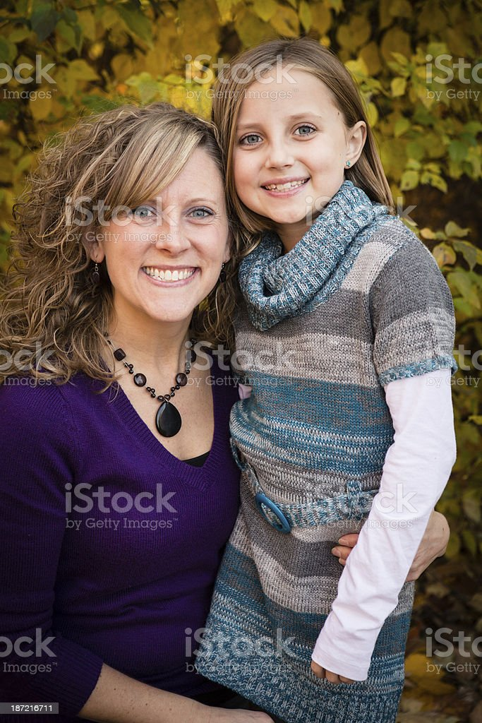 Mother and Her Daughter Standing in Beautiful Autumn Woods royalty-free stock photo