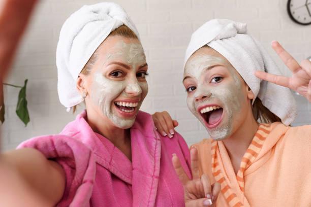 Mutter und ihre Tochter machen Selfie per Smartphone mit Gesichtsmaske auf, Bademantel und Handtuch auf dem Kopf – Foto