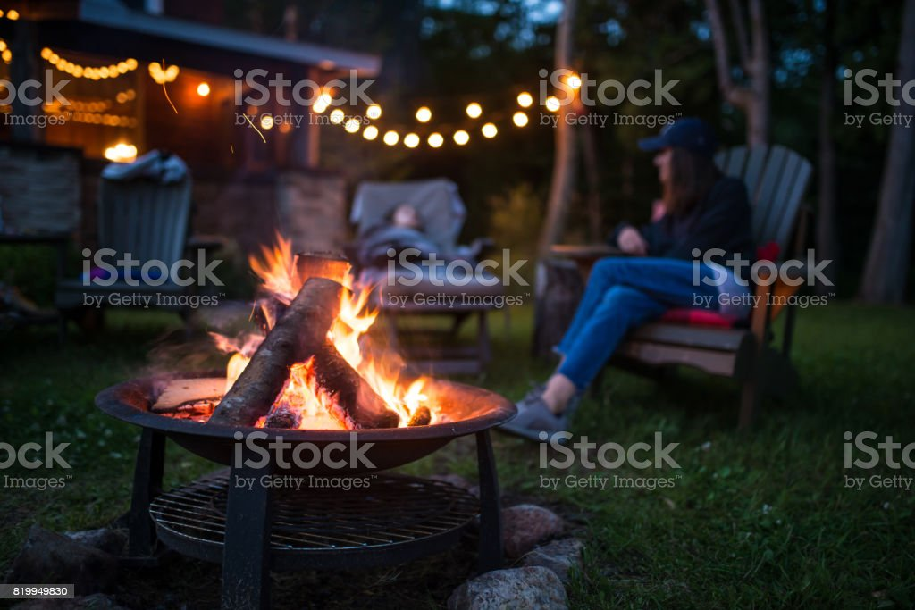 Mother and her daughter warm near campfire late evening  at a beatiful canadian chalet stock photo